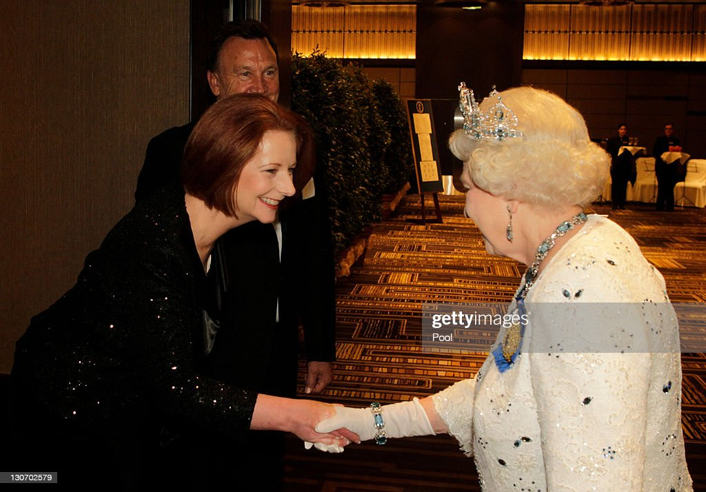 Queen <a gi-track='captionPersonalityLinkClicked' href=/galleries/search?phrase=Elizabeth+II&family=editorial&specificpeople=67226 ng-click='$event.stopPropagation()'>Elizabeth II</a> shakes hands with Australia's Prime Minister <a gi-track='captionPersonalityLinkClicked' href=/galleries/search?phrase=Julia+Gillard&family=editorial&specificpeople=787281 ng-click='$event.stopPropagation()'>Julia Gillard</a>, beside Ms Gillard's partner Tim Mathieson, on arriving at a banquet as part of the Commonwealth Heads of Government Meeting (CHOGM) on October 28, 2011 in Perth, Australia. Queen <a gi-track='captionPersonalityLinkClicked' href=/galleries/search?phrase=Elizabeth+II&family=editorial&specificpeople=67226 ng-click='$event.stopPropagation()'>Elizabeth II</a> opened the 54-nation summit today, following a 9-day tour of Australia. The three-day biennial gathering is chaired by Australian Prime Minister, <a gi-track='captionPersonalityLinkClicked' href=/galleries/search?phrase=Julia+Gillard&family=editorial&specificpeople=787281 ng-click='$event.stopPropagation()'>Julia Gillard</a> and concludes on October 30.