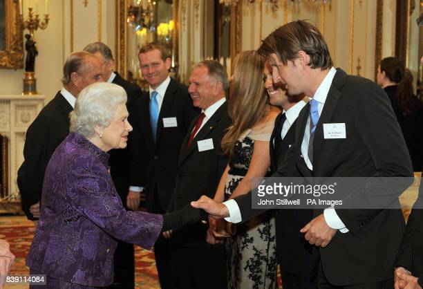 Queen Elizabeth II shakes hands with director Tom Hooper in the white drawing room at Buckingham Palace before a Royal reception for members of the...
