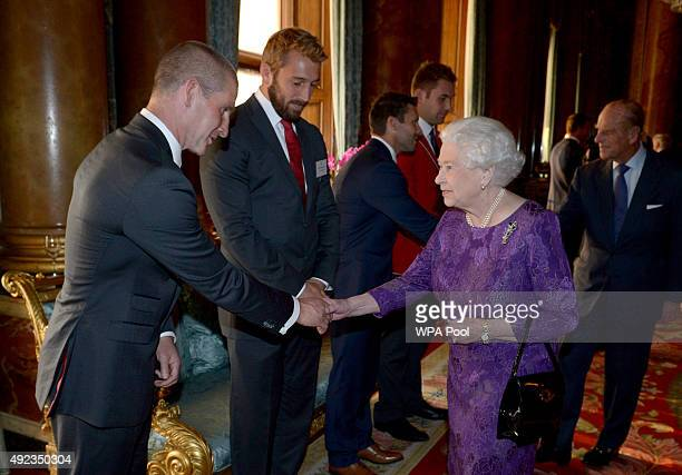 Queen Elizabeth II shakes hands with England Rugby Union head coach Stuart Lancaster as England captain Chris Robshaw looks on during a reception to...