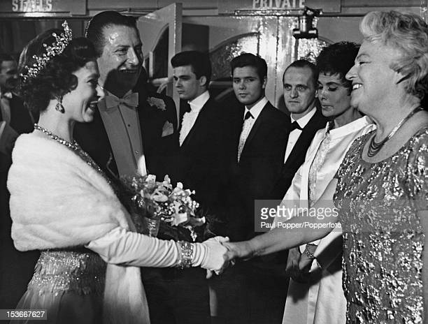 Queen Elizabeth II shakes hands with English singer Gracie Fields at the Royal Variety Performance at the London Palladium 2nd November 1964 Left to...