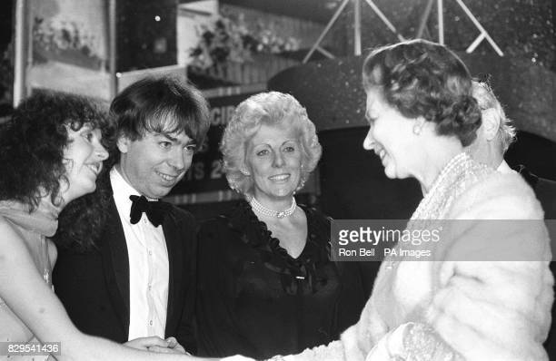 Queen Elizabeth II shakes hands with former Hot Gossip dancer Sarah Brightman girlfriend of composer Andrew LloydWebber at the Apollo Theatre...