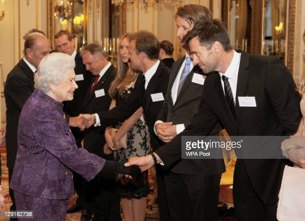 Queen Elizabeth II shakes hands with Hugh Jackman in the white drawing room before a Royal reception for members of the Australian community living...