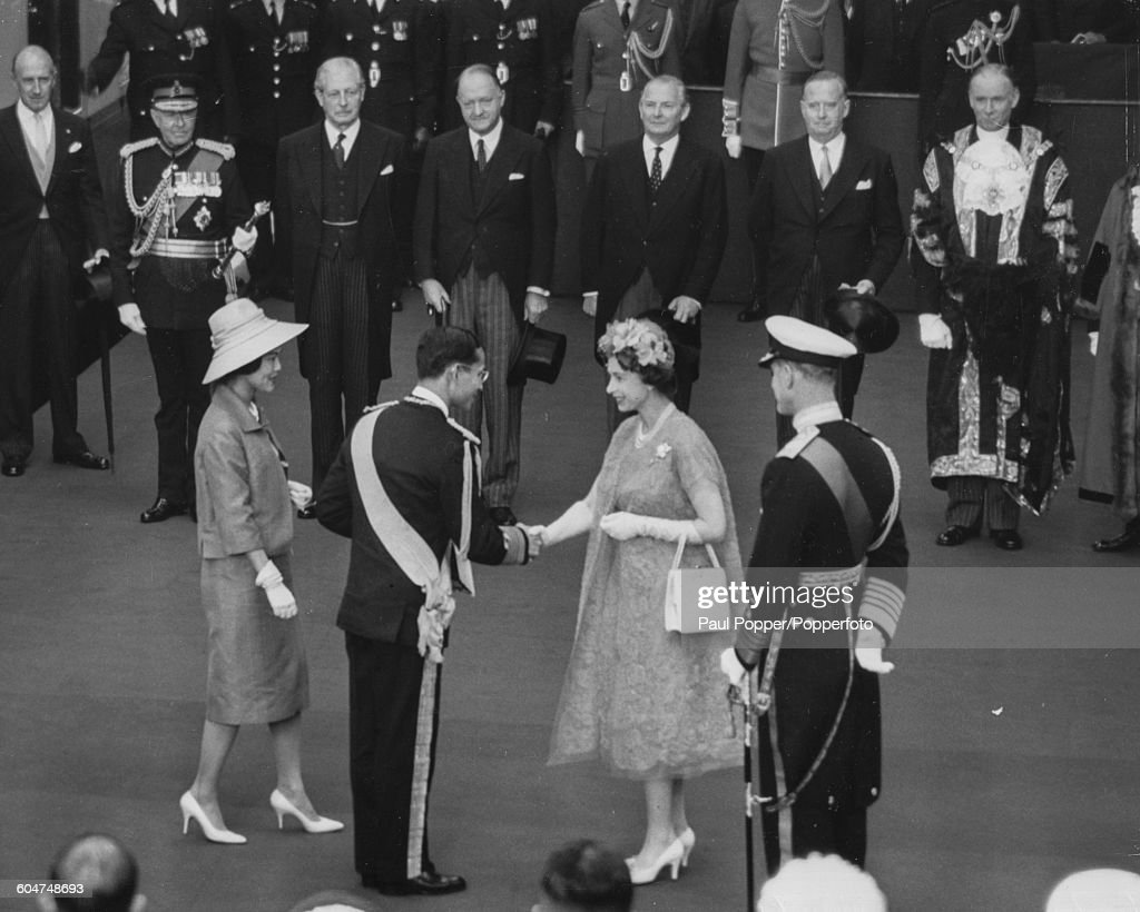 Queen <a gi-track='captionPersonalityLinkClicked' href=/galleries/search?phrase=Elizabeth+II&family=editorial&specificpeople=67226 ng-click='$event.stopPropagation()'>Elizabeth II</a> shakes hands with King Bhumibol Adulyadej of Thailand as Queen <a gi-track='captionPersonalityLinkClicked' href=/galleries/search?phrase=Sirikit&family=editorial&specificpeople=228360 ng-click='$event.stopPropagation()'>Sirikit</a> (left) and <a gi-track='captionPersonalityLinkClicked' href=/galleries/search?phrase=Prince+Philip&family=editorial&specificpeople=92394 ng-click='$event.stopPropagation()'>Prince Philip</a> (right, back to camera) look on, at Victoria Station in London at the start of a two day State Visit on July 19th 1960.