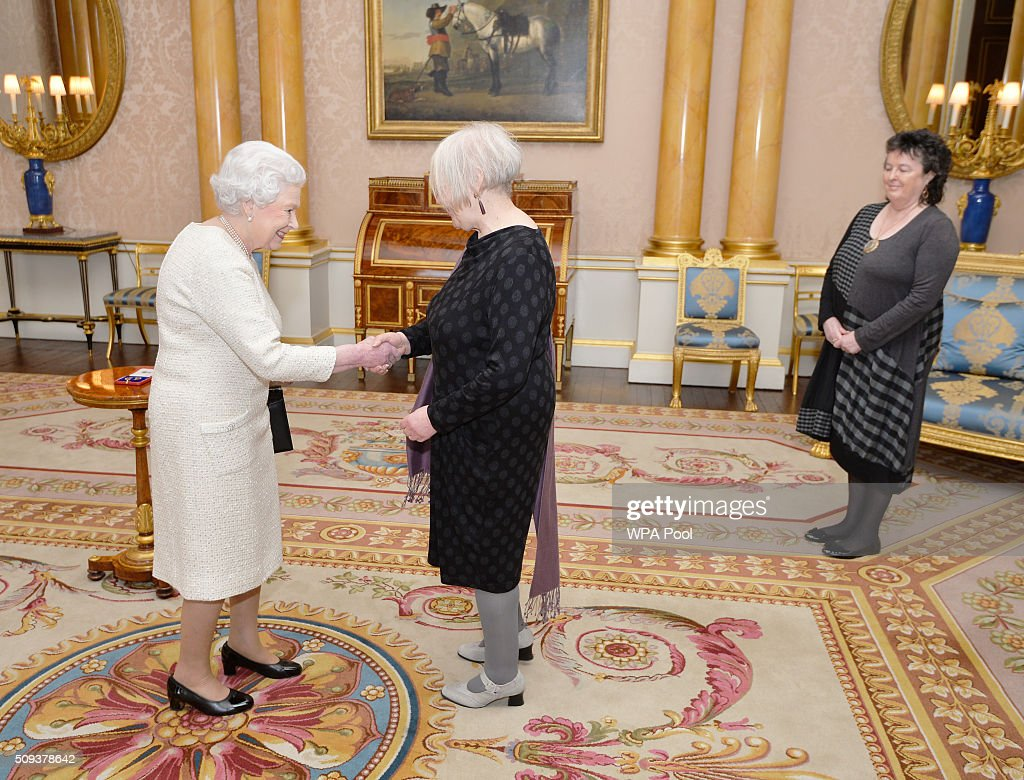 Queen <a gi-track='captionPersonalityLinkClicked' href=/galleries/search?phrase=Elizabeth+II&family=editorial&specificpeople=67226 ng-click='$event.stopPropagation()'>Elizabeth II</a> shakes hands with Liz Lochhead before presenting her with the Queen's Gold Medal for Poetry, accompanied by Poet Laureate Professor Dame Carol Ann Duffy during a private audience, at Buckingham Palace in Westminster on February 10, 2016 in London, England.