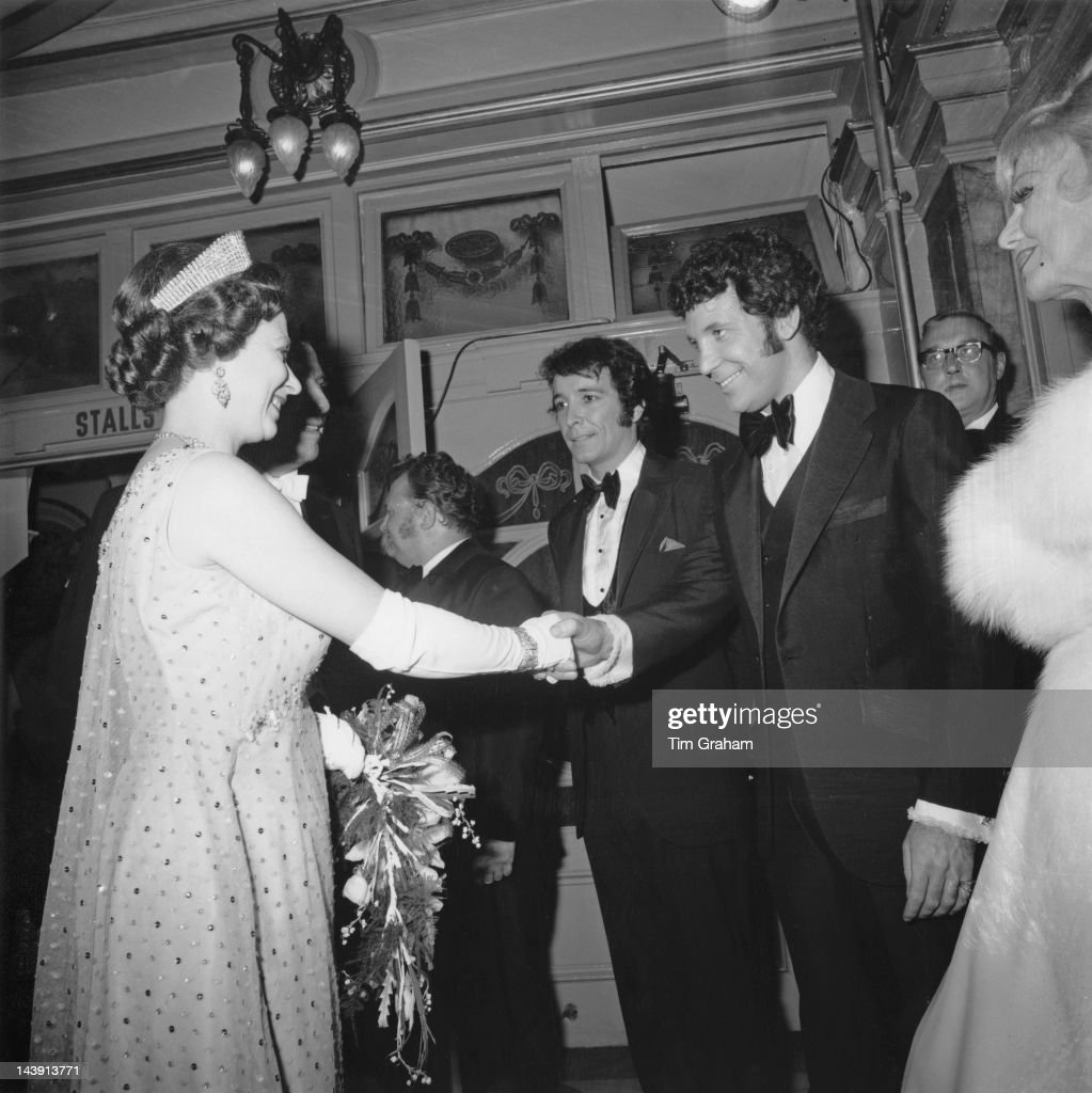 Queen Elizabeth II shakes hands with Welsh singer Tom Jones after the Royal Variety Performance at the London Palladium, 10th November 1969. In the centre is American trumpeter Herb Alpert.