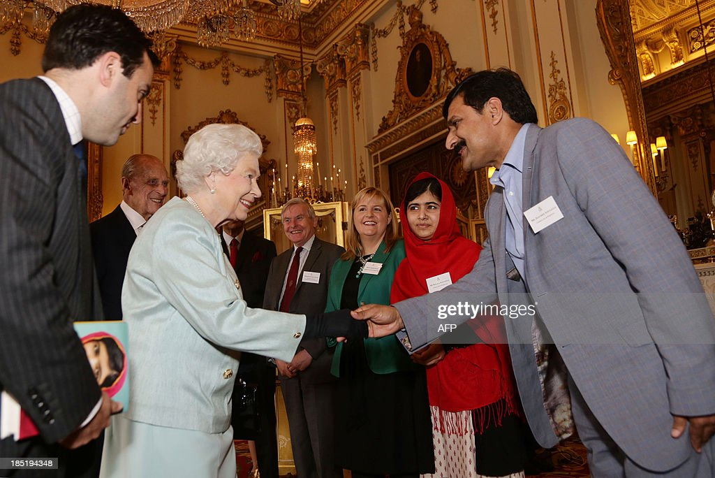 Queen Elizabeth II shakes hands with Ziauddin Yousafzai (R) as Prince Phillip, The Duke of Edinburgh (2-L) and Malala Yousafzai (2-R) look on during a Reception for Youth, Education and the Commonwealth at Buckingham Palace in London on October 18, 2013. The 16-year-old, who was shot by the Taliban for championing girls' rights to an education, met Queen Elizabeth at a reception for youth, education and the Commonwealth. Prince Philip, 92, joked that in Britain, people wanted their children to go to school to get them out of the house -- a comment that left Malala covering her face in a fit of giggles. AFP PHOTO/POOL/Yui Mok