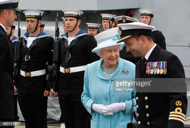 Queen Elizabeth II shares a joke with Commander Peter Laughton Commanding Officer of HMS Lancaster as she visits Portsmouth Naval Base for a tour of...