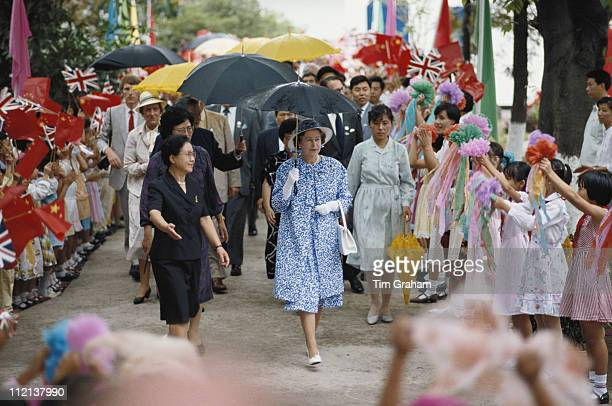 Queen Elizabeth II sheltered by an umbrella meets children at the Children's Palace in Canton during an official State Visit to China 18 October 1986