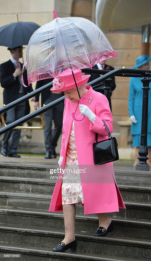 queen-elizabeth-ii-shelters-from-the-rain-under-an-umbrella-as-she-picture-id530213400