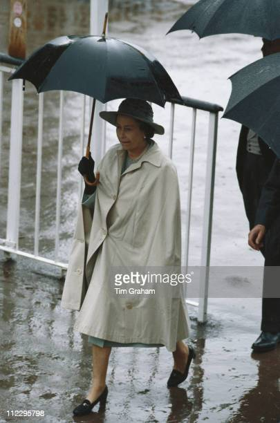 Queen Elizabeth II shelters from the rain under an umbrella at the Royal Ascot race meeting at Ascot racecourse in Ascot Berkshire England Great...