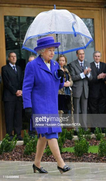 Queen Elizabeth II shelters under an umbrella during her visit to the new National Tennis Centre Roehampton in London on March 29 2007