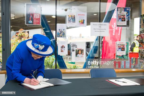 Queen Elizabeth II signs a book on condolence during a visit to the Westway Sports Centre which is providing temporary shelter for those who have...