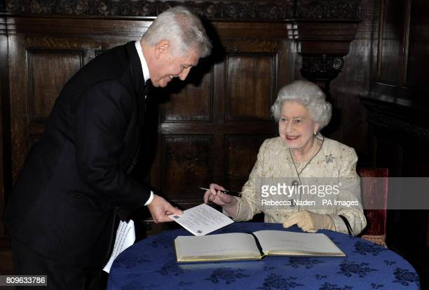 Queen Elizabeth II signs a menu card for Christopher Moran during a reception and dinner to celebrate the 70th Anniversary of The Council of...