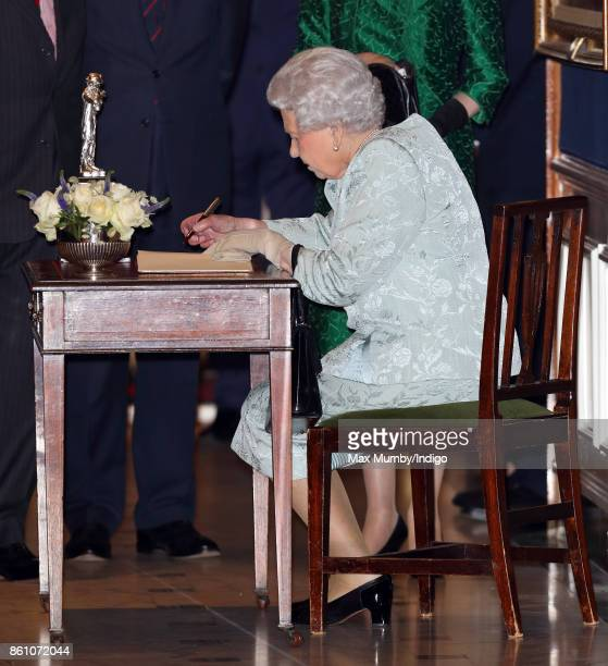 Queen Elizabeth II signs a visitors book as she attends a reception to mark the Centenary of the Women's Royal Navy Service and the Women's Auxiliary...