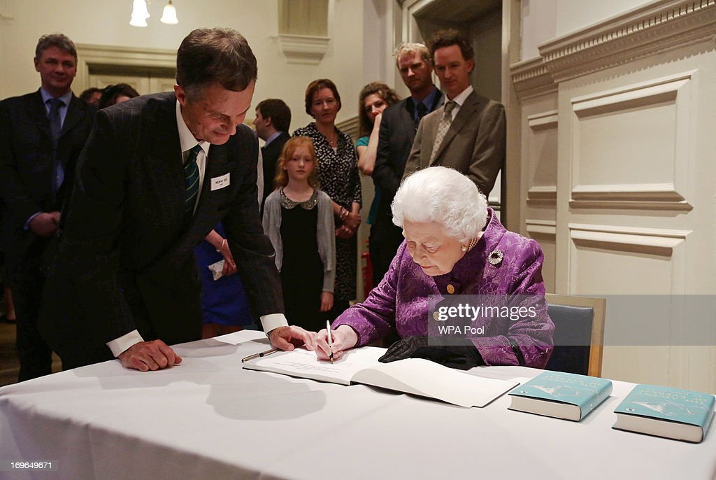 Queen <a gi-track='captionPersonalityLinkClicked' href=/galleries/search?phrase=Elizabeth+II&family=editorial&specificpeople=67226 ng-click='$event.stopPropagation()'>Elizabeth II</a> signs the guest book as Henry Day, Chairman of the Mount Everest Foundation, looks on during a reception to celebrate the 60th Anniversary of the ascent of Everest, at the Royal Geographical Society in Kensington, on May 29, 2013 in Kensington, West London, England.