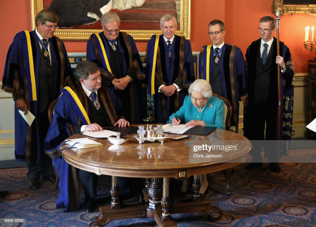Queen Elizabeth II signs the Instrument, which is a document, written on vellum, and formally records Her Majesty's attendance at the lunch to celebrate the 70th anniversary of her becoming a Freeman of the Company at Drapers' Hall on the occasion of the 70th Anniversary of Her Majesty's Admission to the Freedom of the Company on May 31, 2017 in London, England.