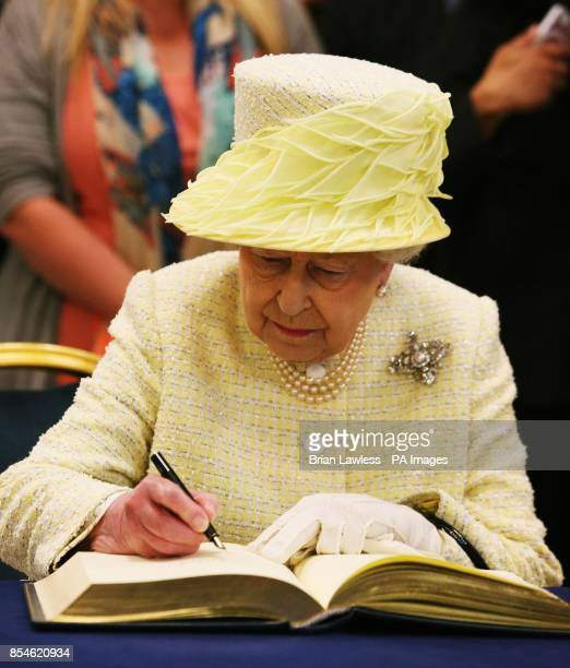 Queen Elizabeth II signs the visitor book ahead of her departure from City Hall Belfast during a three day Royal visit to Northern Ireland