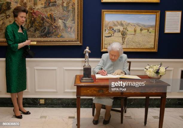 Queen Elizabeth II signs the visitors book watched by Princess Anne following a reception to celebrate the Women's Royal Naval Service 100 project at...