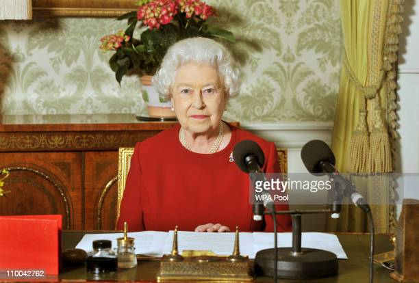 Queen Elizabeth II sits at a desk with microphones after recording her Commonwealth Day address that is broadcast across the world at Buckingham...