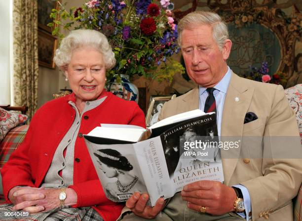 Queen Elizabeth II sits with the Prince Charles Prince of Wales and studies one of the first copies of ' Queen Elizabeth The Queen Mother The...