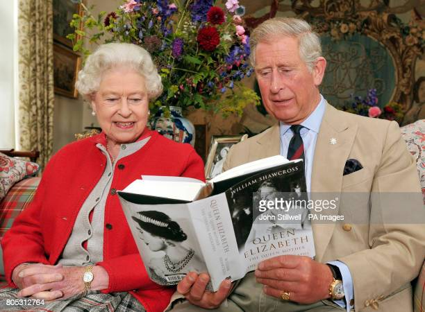 Queen Elizabeth II sits with the Prince of Wales and studies one of the first copies of ' Queen Elizabeth the Queen mother the official biography' in...