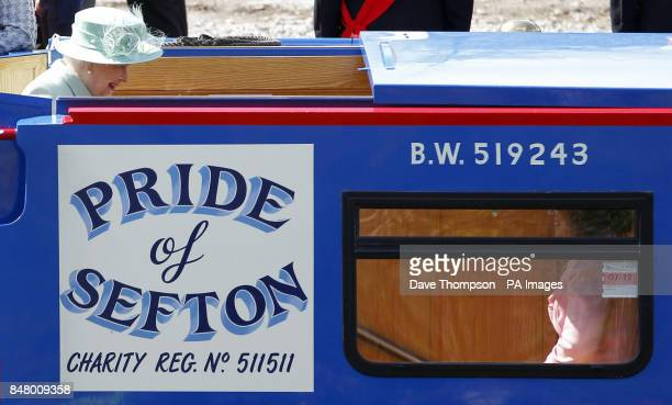 Queen Elizabeth II smiles as she boards a canal barge called the Pride Of Sefton before making her way along the Leeds and Liverpool canal with the...