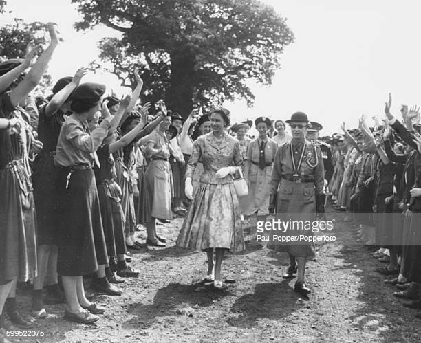 Queen Elizabeth II smiles as she is greeted by a group of girl guides during a visit to the Guide World Camp in Windsor Great Park England on August...