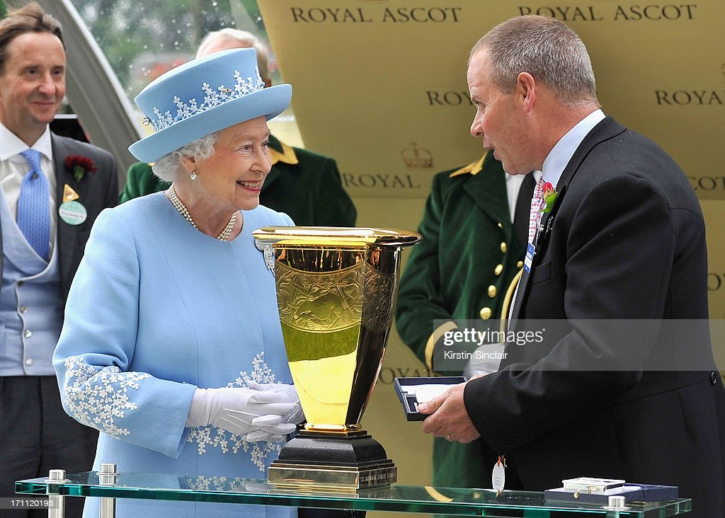 Queen Elizabeth II smiles as she presents Diamond Jubilee Stakes trophy to trainer Clive Cox after he won riding Lethal Force during day five of Royal Ascot at Ascot Racecourse on June 22, 2013 in Ascot, England.