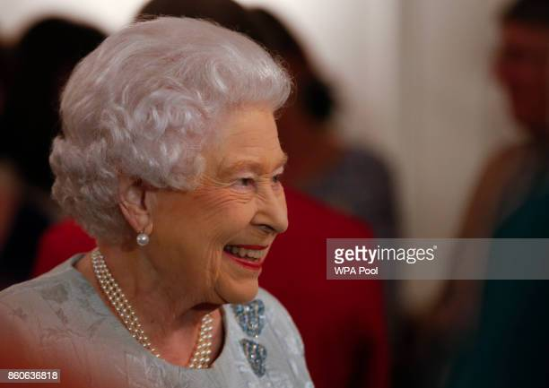 Queen Elizabeth II smiles as she talks to guests at a reception to celebrate the Women's Royal Naval Service 100 project at The Army and Navy Club on...