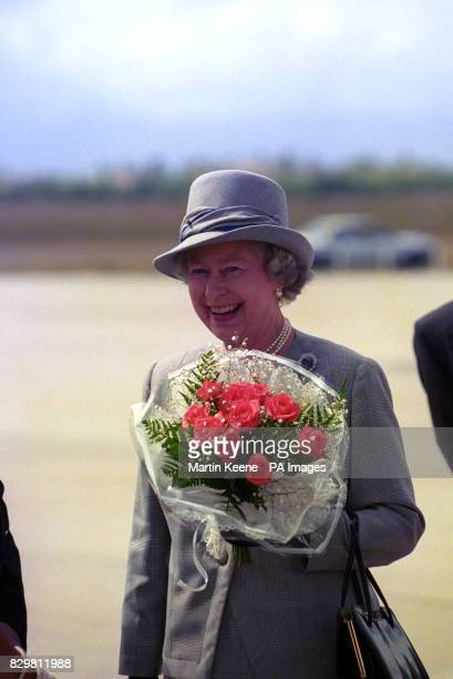 Queen Elizabeth II smiles as she walks on South African soil for the first time since 1947 on her arrival at Cape Town's DF Malan Airport