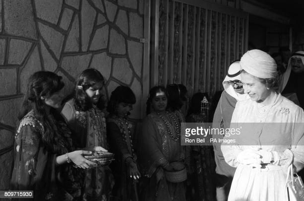 Queen Elizabeth II smiles at girls in national costume during a visit to Bahrain Museum at Muharraq where she was given a pottery jar more than 4000...