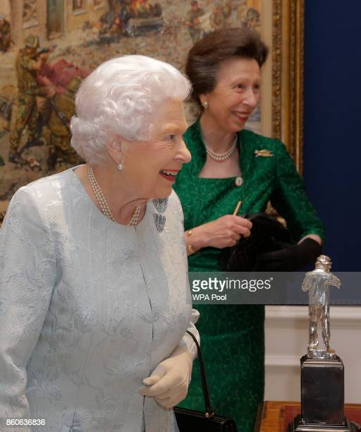 Queen Elizabeth II smiles with Princess Anne behind during a reception to celebrate the Women's Royal Naval Service 100 project at The Army and Navy...