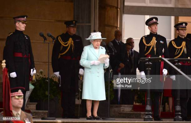 Queen Elizabeth II speaks during a ceremony to present new colours to the 1st Battalion and and F Company Scots Guards at Buckingham Palace on May 18...