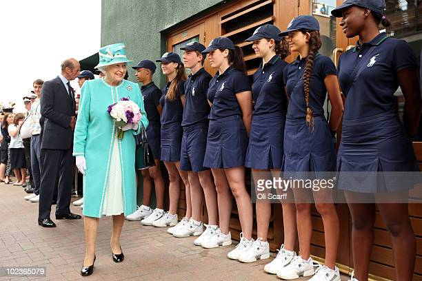 Queen Elizabeth II speaks to ball boys and girls as she attends the Wimbledon Lawn Tennis Championships on Day 4 at the All England Lawn Tennis and...
