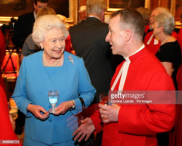 Queen Elizabeth II speaks to Chaplain Hugh Bearn at a reception for the College of Chaplains at Windsor Castle in Windsor Berkshire