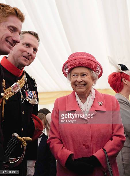 Queen Elizabeth II speaks to soldiers and their families following the amalgamation parade of The Queen's Royal Lancers and 9th/12th lancers at...