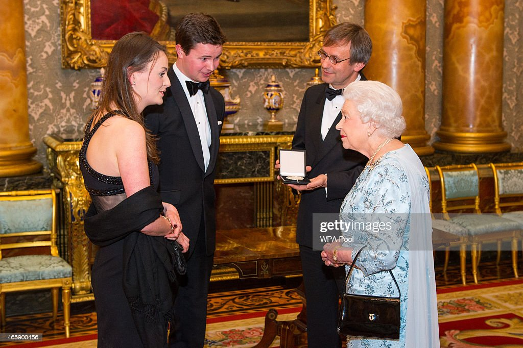 Queen Elizabeth II speaks to the winner of the 2014 Queen's Medal for Music Simon Halsey (right) and his children Harriett (left) and Jonathan (second left), during a reception to mark the conclusion of the 'Moving Music' campaign and the long association of conductor Michael Tilson Thomas with the London Symphony Orchestra, at Buckingham Palace on March 11, 2015 in London, United Kingdom.