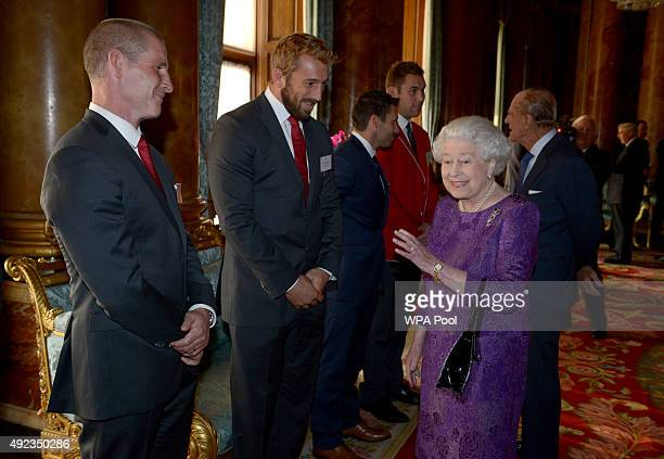 Queen Elizabeth II speaks with England Rugby Union head coach Stuart Lancaster and England captain Chris Robshaw during a reception to mark the Rugby...