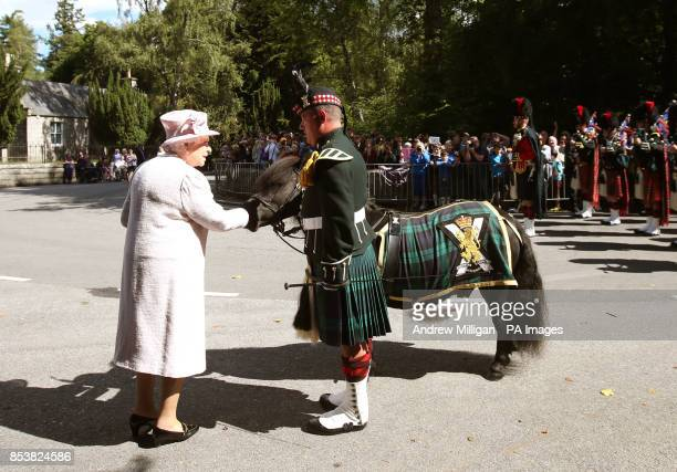 Queen Elizabeth II speaks with Major Corporal Mark Wilkinson with pony Cruachan IVthe mascot of the Royal Regiment of Scotland as she inspects the...
