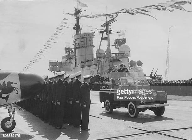 Queen Elizabeth II standing in the back of a series II Land Rover as it drives past a guard of honour on the deck of HMS Eagle Britain's largest...