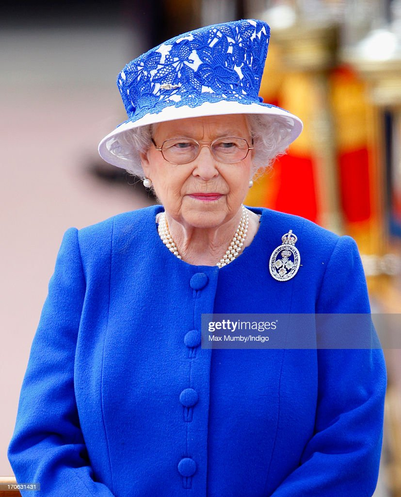 Queen Elizabeth II stands on a dais outside Buckingham Palace during the annual Trooping the Colour Ceremony on June 15, 2013 in London, England. Today's ceremony which marks the Queen's official birthday will not be attended by Prince Philip the Duke of Edinburgh as he recuperates from abdominal surgery. This will also be The Duchess of Cambridge's last public engagement before her baby is due to be born next month.