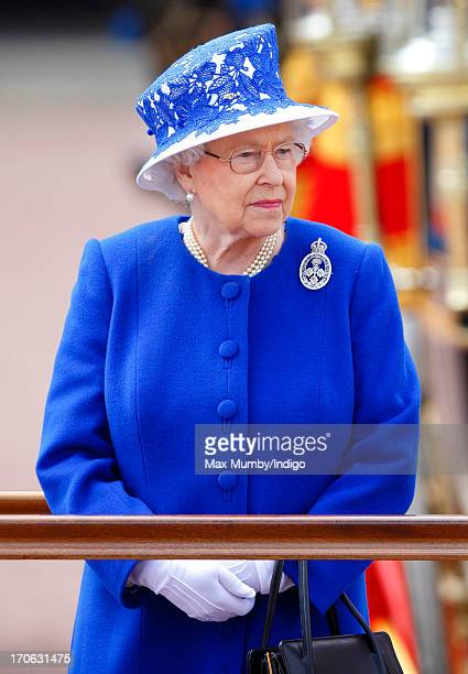 Queen Elizabeth II stands on a dais outside Buckingham Palace during the annual Trooping the Colour Ceremony on June 15 2013 in London England...