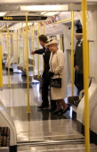 Queen Elizabeth II stands onboard a train as she makes an official visit to Baker Street Underground Station to mark 150th anniversary of the London...