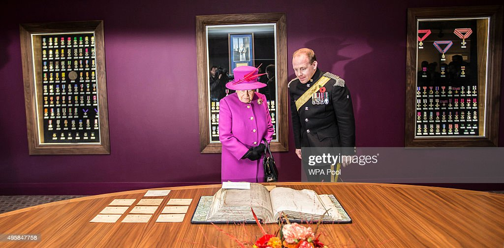 Queen Elizabeth II stands with Major Terry Warburton during a visit to the medal room in the Ministry of defence medal office at the joint casualty and compassionate centre within Imjin barracks on November 5, 2015 in Innsworth, Gloucestershire, United Kingdom.