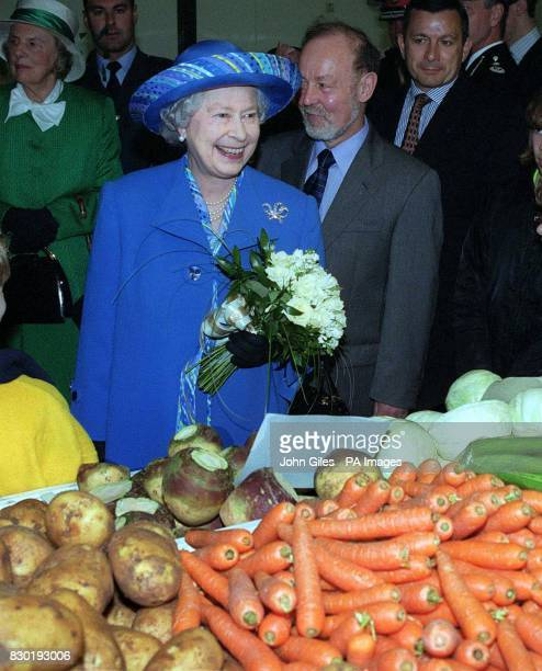 Queen Elizabeth II stops to look at vegetables on sale at a Market Stall in Hull during a walkabout in the City as part of the Hull 700 celebrations...
