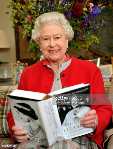 Queen Elizabeth II studies one of the first copies of ' Queen Elizabeth the Queen mother the official biography' in a living room at Birkhall the...