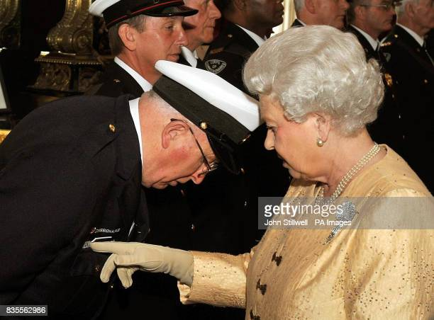 Queen Elizabeth II studies the name badge of John McIntosh from Canada during a reception for the Corps of Commissionaires in honour of their 150th...