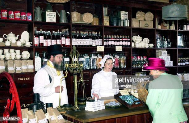 Queen Elizabeth II takes an interest whilst visiting a 19th century style store complete with costumed staff during her visit with the Duke of...