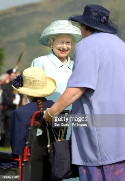 Queen Elizabeth II talks to Elaine Flaws and her daughter Jacqueline at a garden party held at Holyrood House in Edinburgh More than 8000 people from...