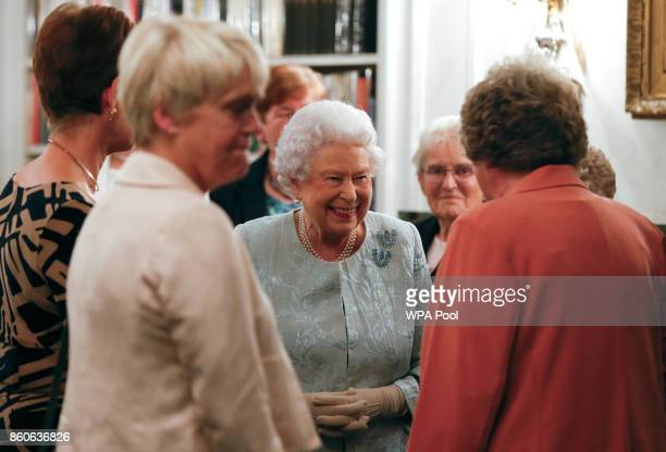 Queen Elizabeth II talks to guests at a reception to celebrate the Women's Royal Naval Service 100 project at The Army and Navy Club on October 12...